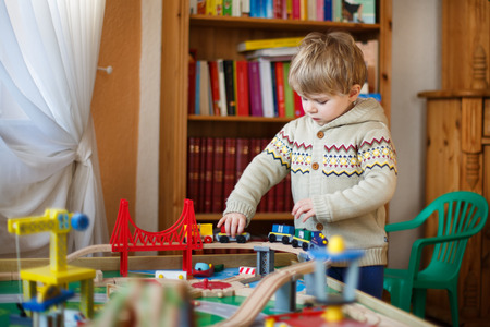 wood railroad: Little toddler boy playing with wooden railway, indoors. Stock Photo