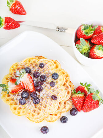 Crisp golden fresh baked waffle topped with strawberries and blueberries on white table photo