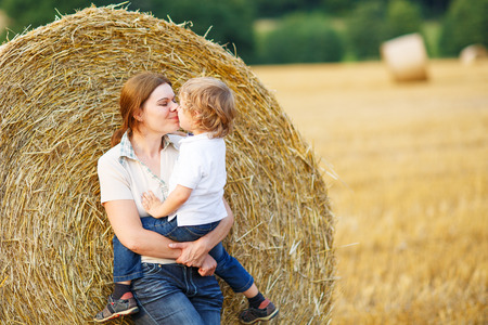 Young mother and her little son together on yellow hay field in summer photo
