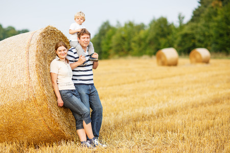 happy family of three: mother, father and little toddler son on yellow hay field in summer photo