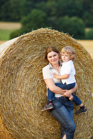 Young mother and her little son having fun on yellow hay field in summer photo