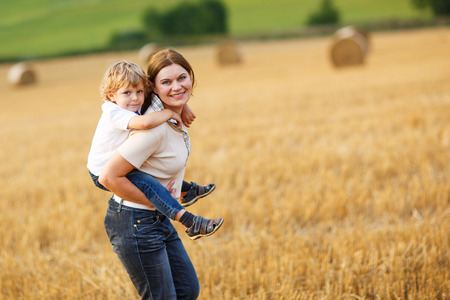 Happy family of two: Young mother and little toddler boy walking on yellow hay field in summer photo