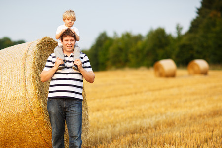 Happy family of two: Young father and his little son having fun on yellow hay field in summer photo