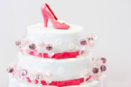 Delicious beautiful wedding cake in white and red with cake pops and chocolate bride shoe