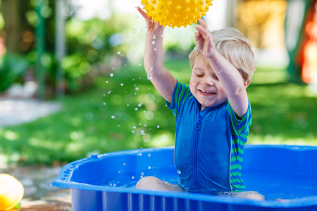 kiddie: Little toddler boy having fun with splashing water and playing ball in summer garden pool