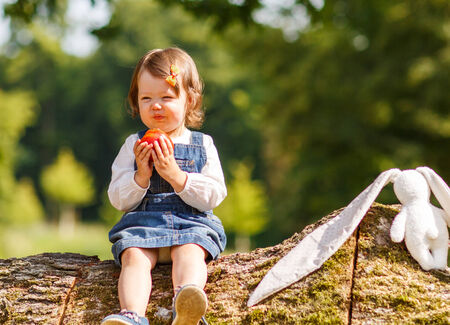 Little baby girl eating fresh apple in summer park photo