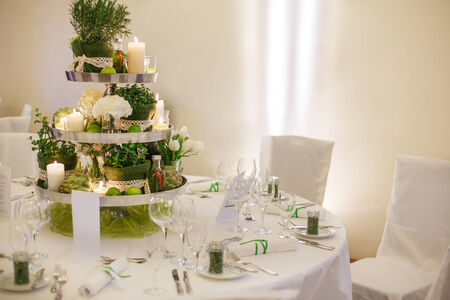 wedding table decor: Beautiful table set  for green wedding or event party, indoors with big flower and candle arrangement Stock Photo