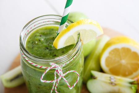 サラダ、リンゴ、キュウリ、パイナップル、健康的な飲み物としてレモンの新鮮な有機緑のスムージー 写真素材