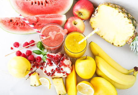 Fresh organic red and yellow smoothie with apple, watermelon, pomegranate, raspberry, pineapple, banana and mango photo