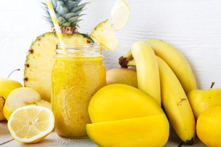 mango fruta: Smoothie amarillo orgánico fresco con plátano, manzana, mango, pera, piña y limón como bebida saludable