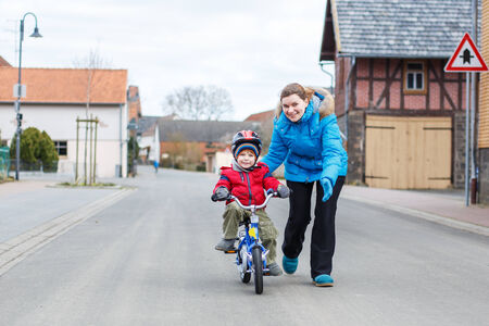 Young mother teaching her 3 years old little son to ride a bike, outdoors photo