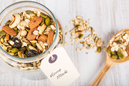 Homemade healthy cereals granola with different nuts and oats in jar on wooden background photo