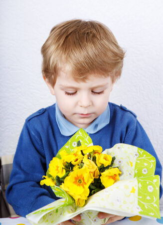 mother'sday: Cute lovely toddler boy of 3 years sniffing yellow flowers for mothersday, indoor