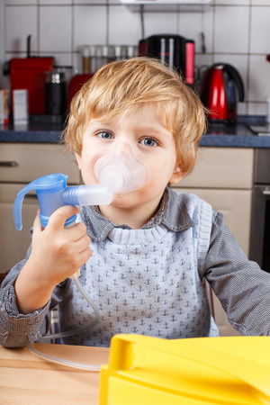 Adorable toddler boy making inhalation with nebulizer and inhalator in home kitchen Stock Photo - 26446712