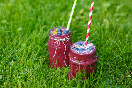 Fresh smoothie drink with different berries as healthy breakfast. On green grass background photo