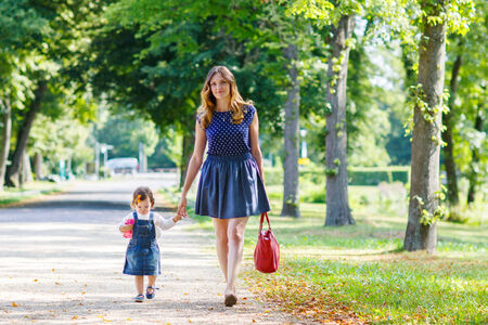 Young woman and little girl of one year walking through summer park photo