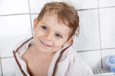 Portrait of lovely little toddler boy of two or three years after taking bath with a bath towel photo