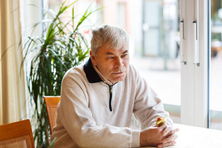 Portrait of senior man near window, indoor Stock Photo - 26447342