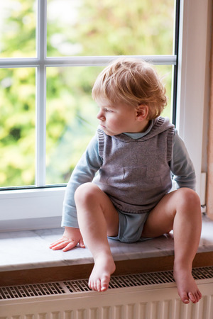Adorable blond toddler boy looking out of the window, indoors photo