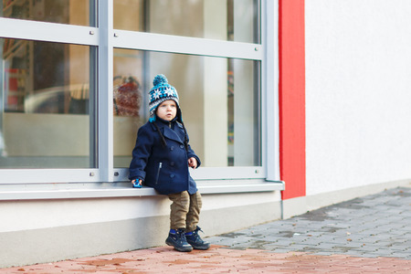 Little boy sitting infront of big window in the city, outdoors, winter. photo