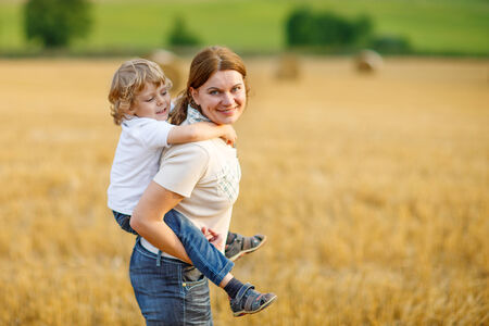 Happy family of two: Young mother and her little son having fun on yellow hay field in summer photo