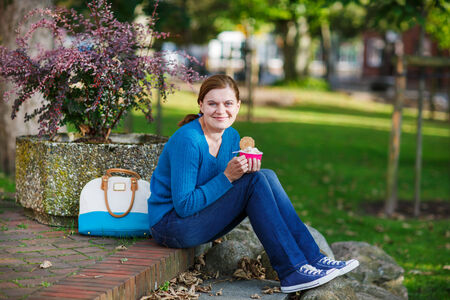 Young woman eating ice cream in summer park photo