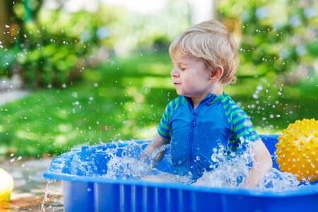kiddie: Little toddler boy having fun with splashing water in summer garden pool