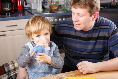 Little boy and his father making inhalation with nebuliser in home kitchen Stock Photo - 26447554