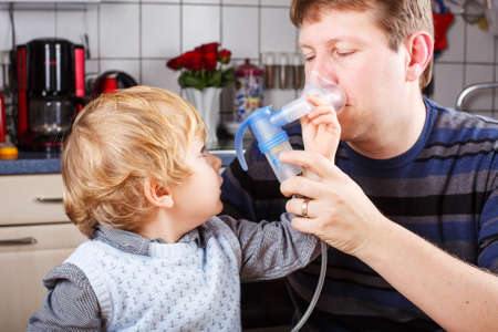 Little boy and his father making inhalation with nebuliser in home kitchen Stock Photo - 26447555