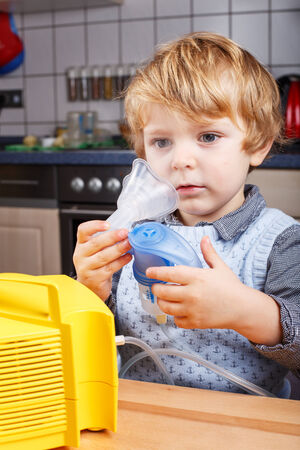 Adorable toddler boy making inhalation with nebulizer and inhalator in home kitchen Stock Photo - 26447556