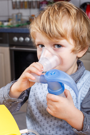 Adorable toddler boy making inhalation with nebulizer and inhalator in home kitchen Stock Photo - 26447559
