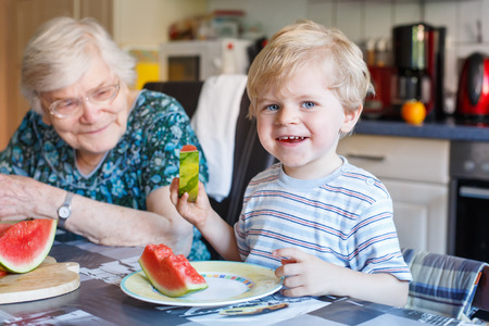 Two generations: Little boy and his great grandmother eating watermelon in home kitchen. Selective focus on child