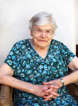 the nineties: Happy senior woman relaxing in summer garden