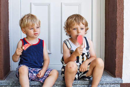 Two little twins boys eating ice cream in summer, outdoors