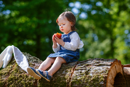 Little cute baby girl eating fruit in summer forest photo
