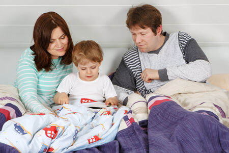 Happy family: Mother, father and little son reading book before going to bed photo