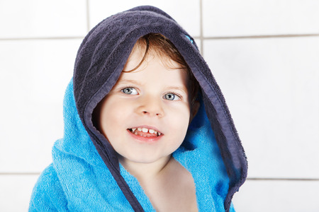 Portrait of lovely little toddler boy of two years after taking bath with a bath towel photo