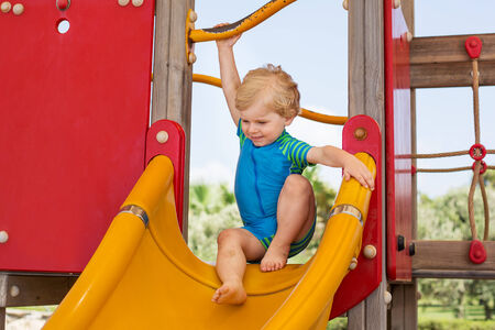 Little toddler boy having fun on playground in summer photo