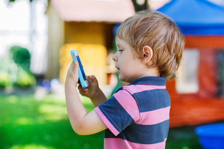 Beautiful little boy taking picture with mobile in summer garden photo