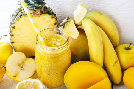 Fresh organic yellow smoothie with banana, apple, mango, pear, pineapple and lemon as healthy drink photo