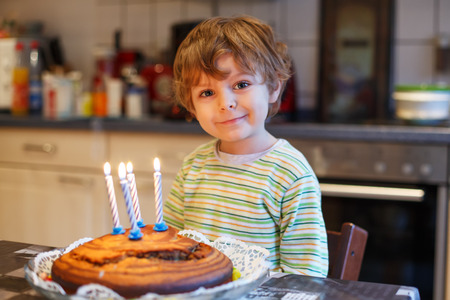 Little boy celebrating birthday and blowing candles photo