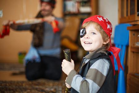 Malý předškolním chlapec 4 roky slaví narozeniny v pirátském kostýmu, v interiéru s otcem na pozadí