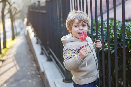 Little caucasian toddler boy of two years having fun in spring city, outdoors photo