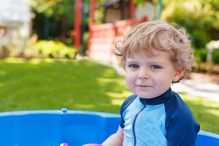 Adorable blond toddler boy playing with water in summer garden on sunny day, outdoors. photo