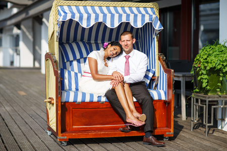 Beautiful indian bride and caucasian groom, in beach chair photo