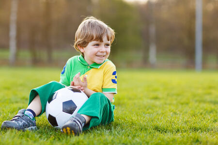 alone boy: Happy blond little boy of 4 playing soccer with football on football field, outdoors.