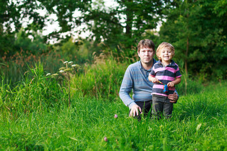 Little boy and his father sitting on grass in summer forest near lake photo