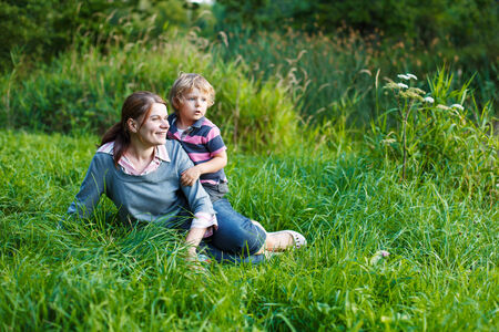 Little boy and his mother sitting on grass in summer forest near lake photo