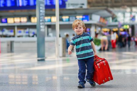 Funny chlapec děje na dovolenou výlet s kufrem na letišti, v interiéru. Reklamní fotografie