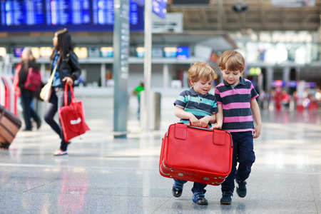 Two little sibling boys having fun and going on vacations trip with suitcase at airport, indoors. Stock Photo